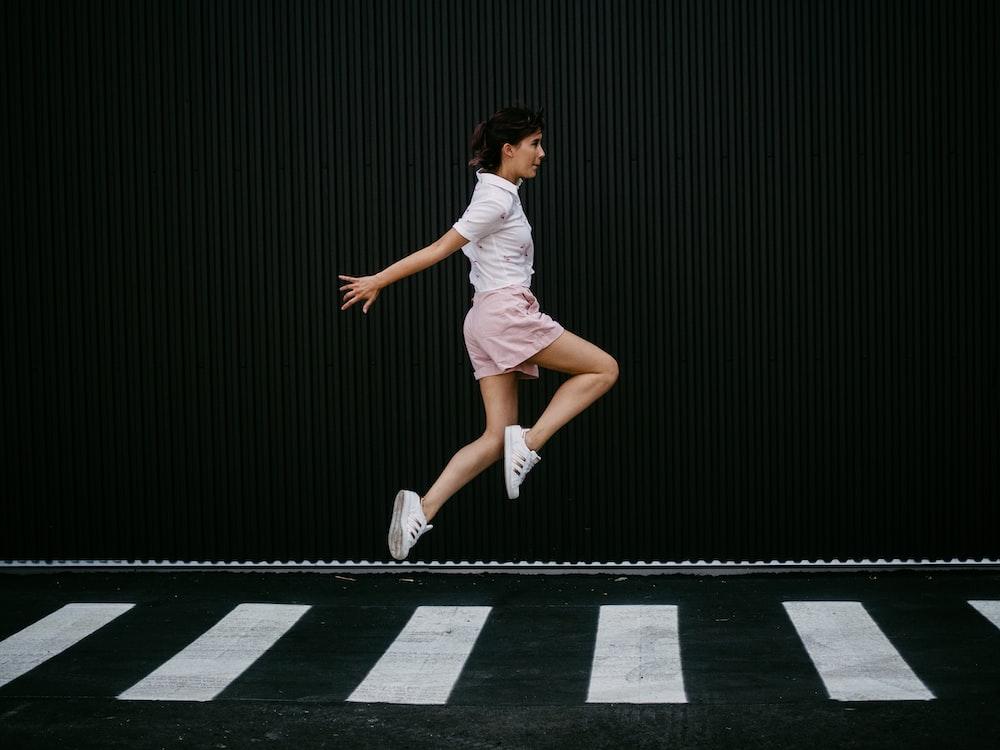 woman jumping on pedestrian lane