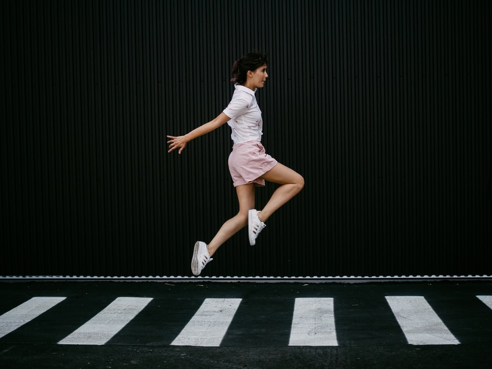 woman jumping on pedestrian lane