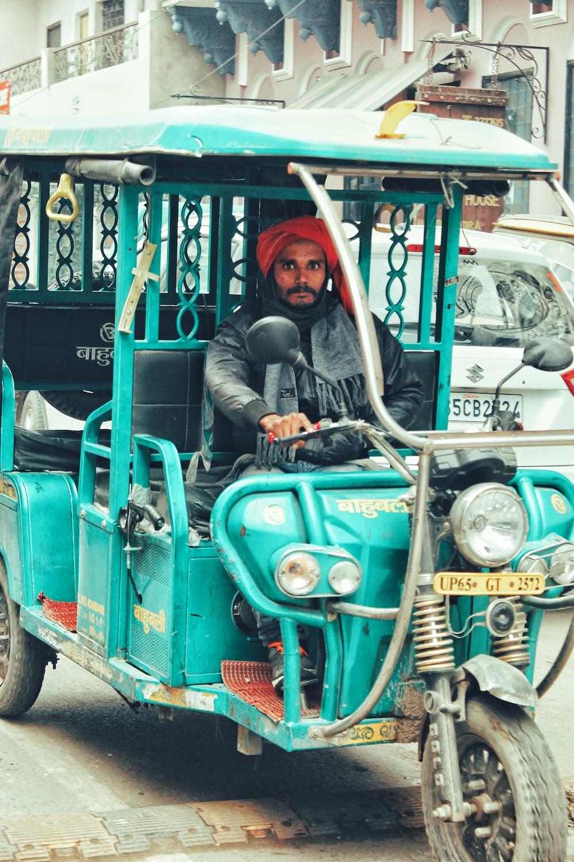 man driving auto-rickshaw during daytime