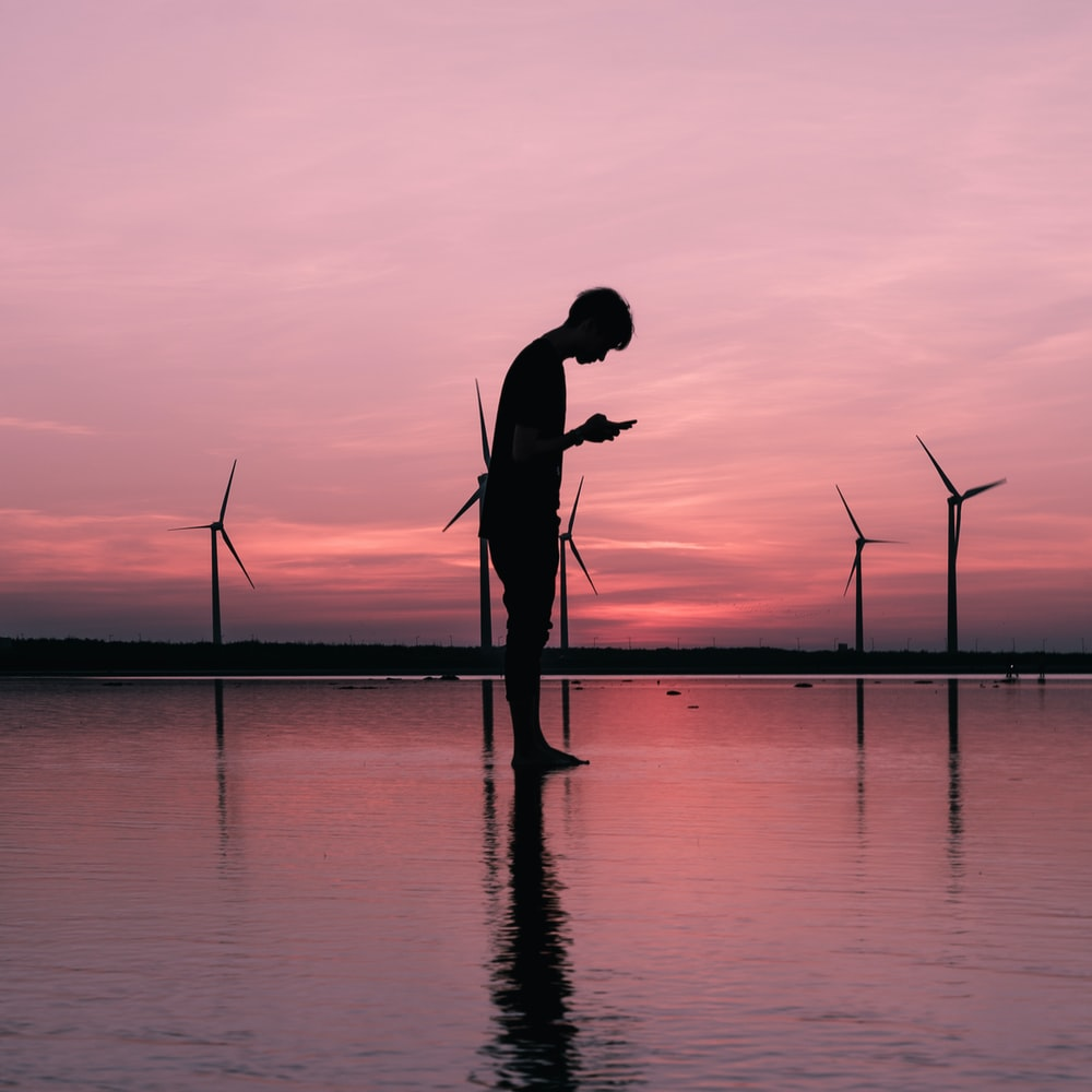 silhouette photography of man standing while using smartphone