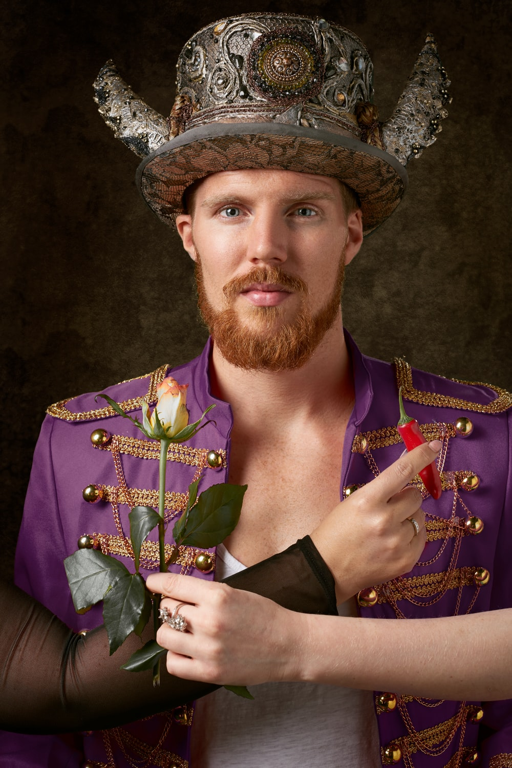 man wearing purple coat and gold hat