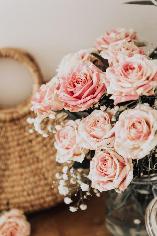 pink rose flower centerpiece beside brown handbag