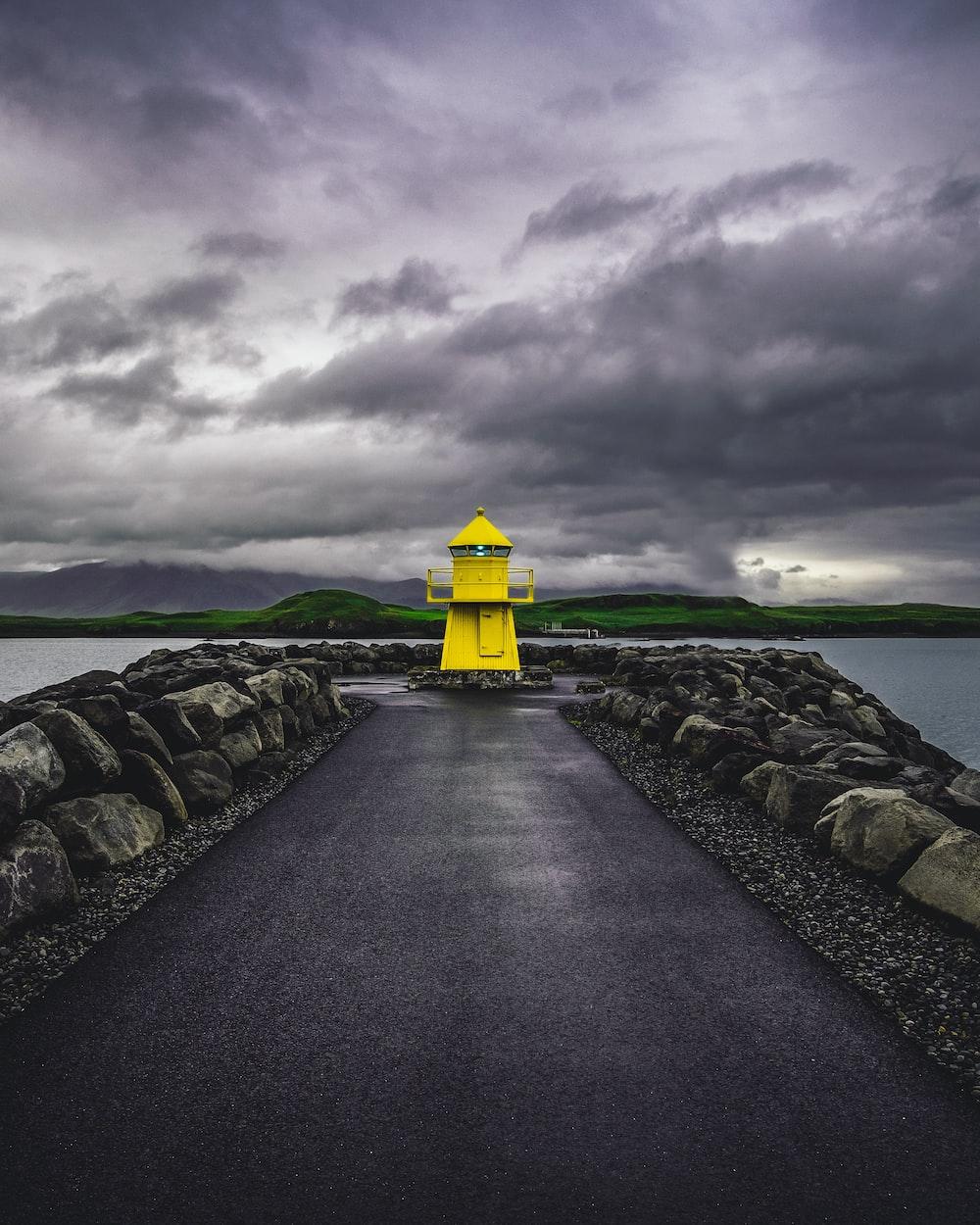 yellow lighthouse beside sea