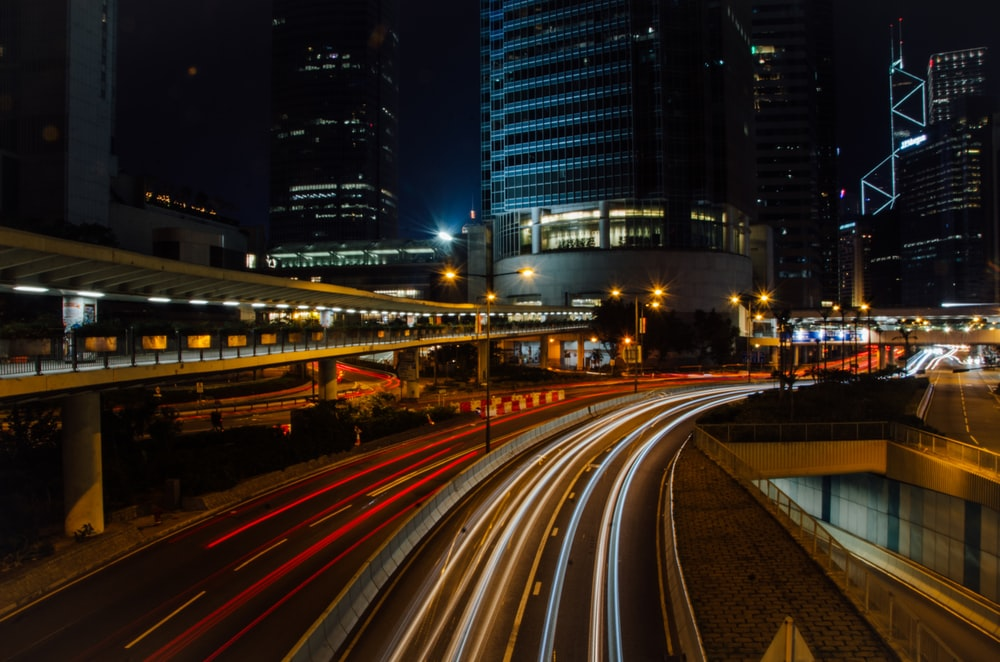 time lapse photography of cars between buildings