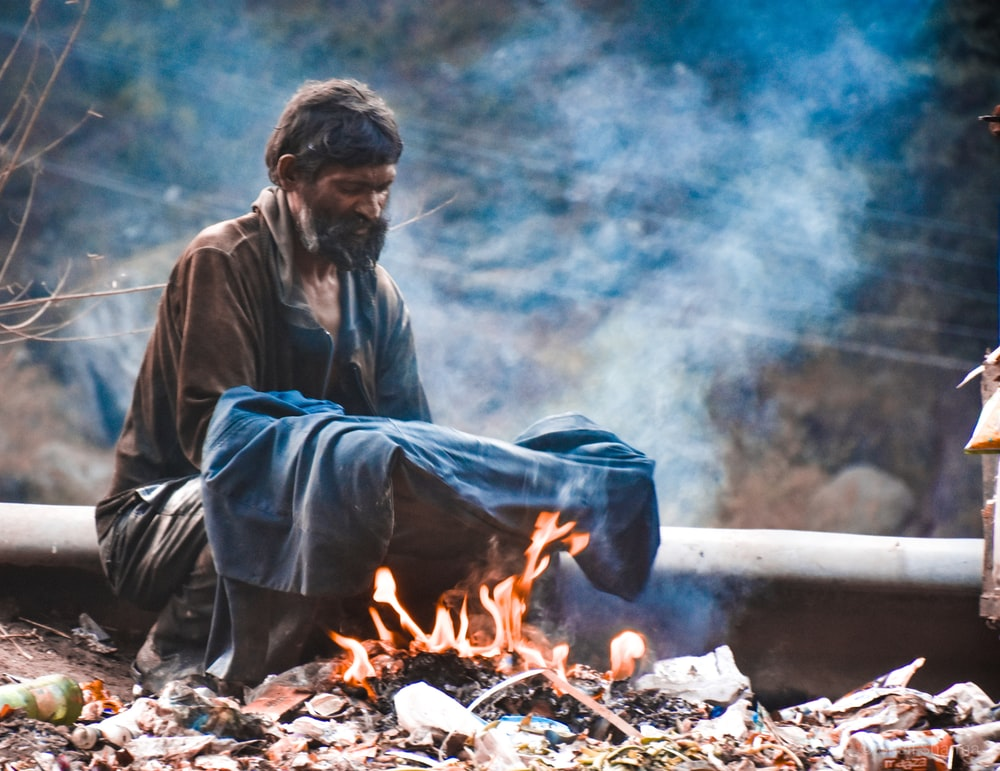 man heating clothing on fire