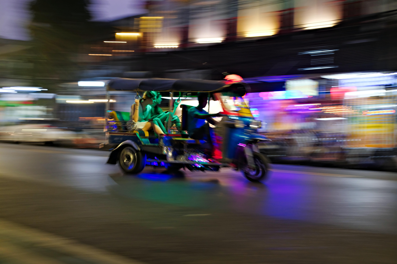 people rides tuk-tuk in lighted city street