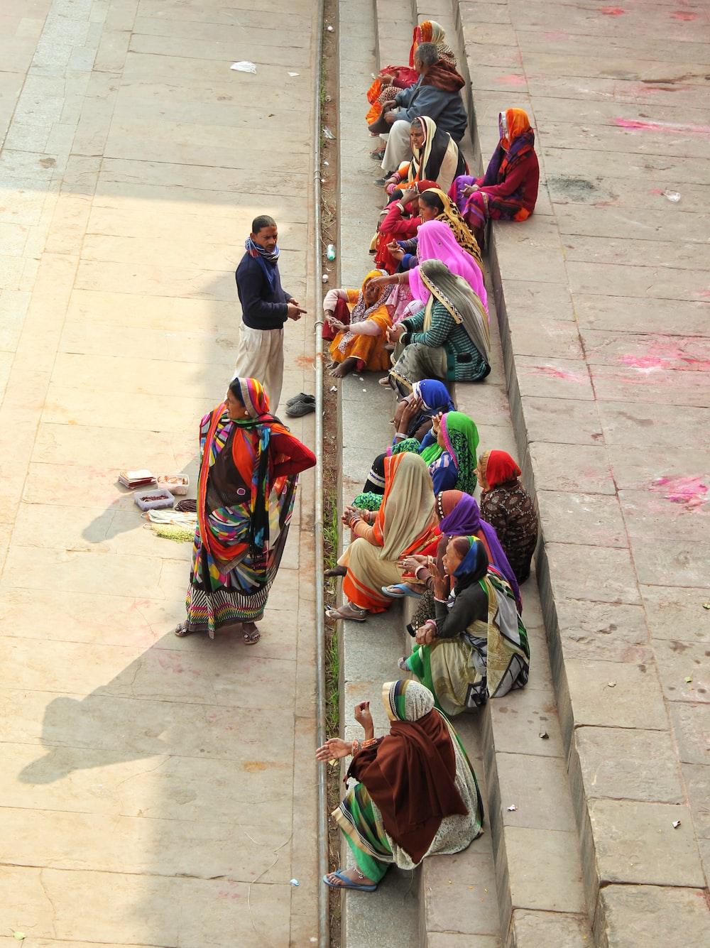 women wearing sari dress sitting on concrete stairs during daytime