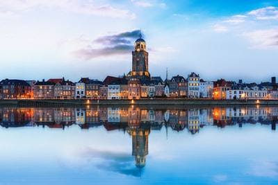 lighted buildings across placid lake netherlands zoom background