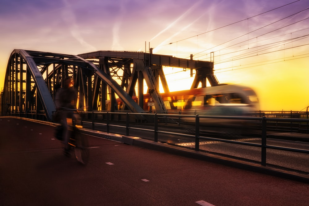 time-lapse photography of biker passing road beside trail during golden hour