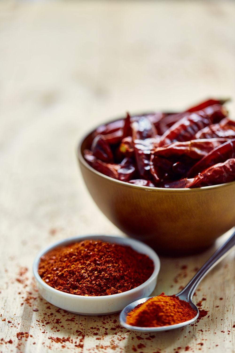 bowl of red chilis and spoon of chili powder