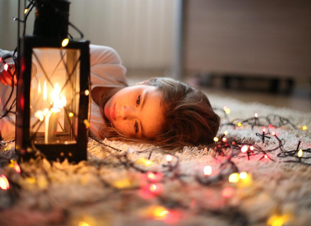 selective focus photography of of girl beside black lantern