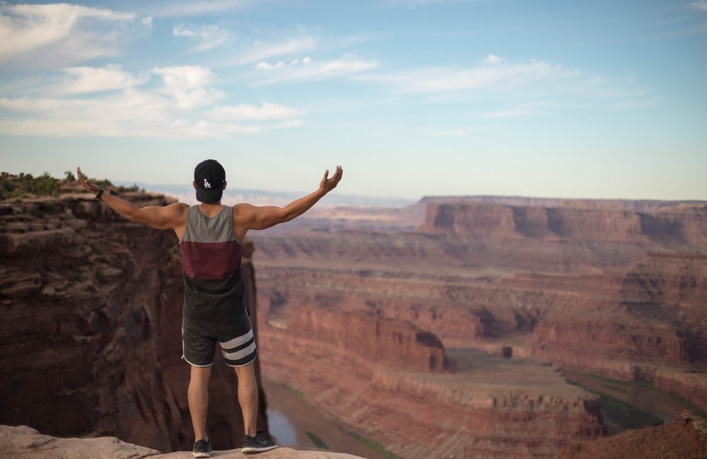 man wearing tank top standing on top of cliff