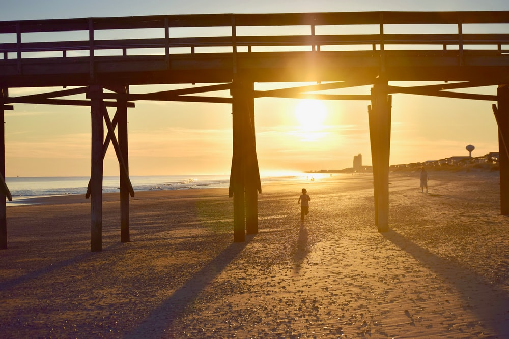 2 people jogging in beach under wooden dock at dusk