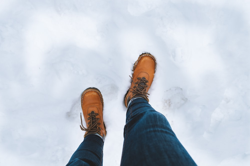man wearing brown boots walking in icy surface