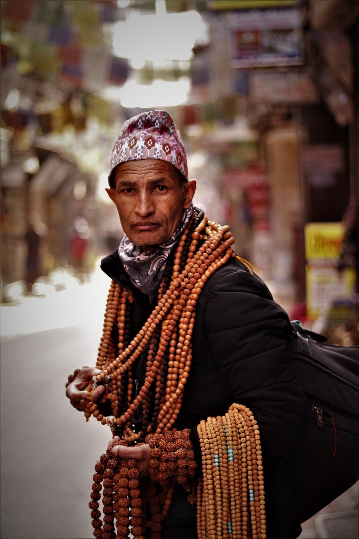 man carrying brown beads while walking on street