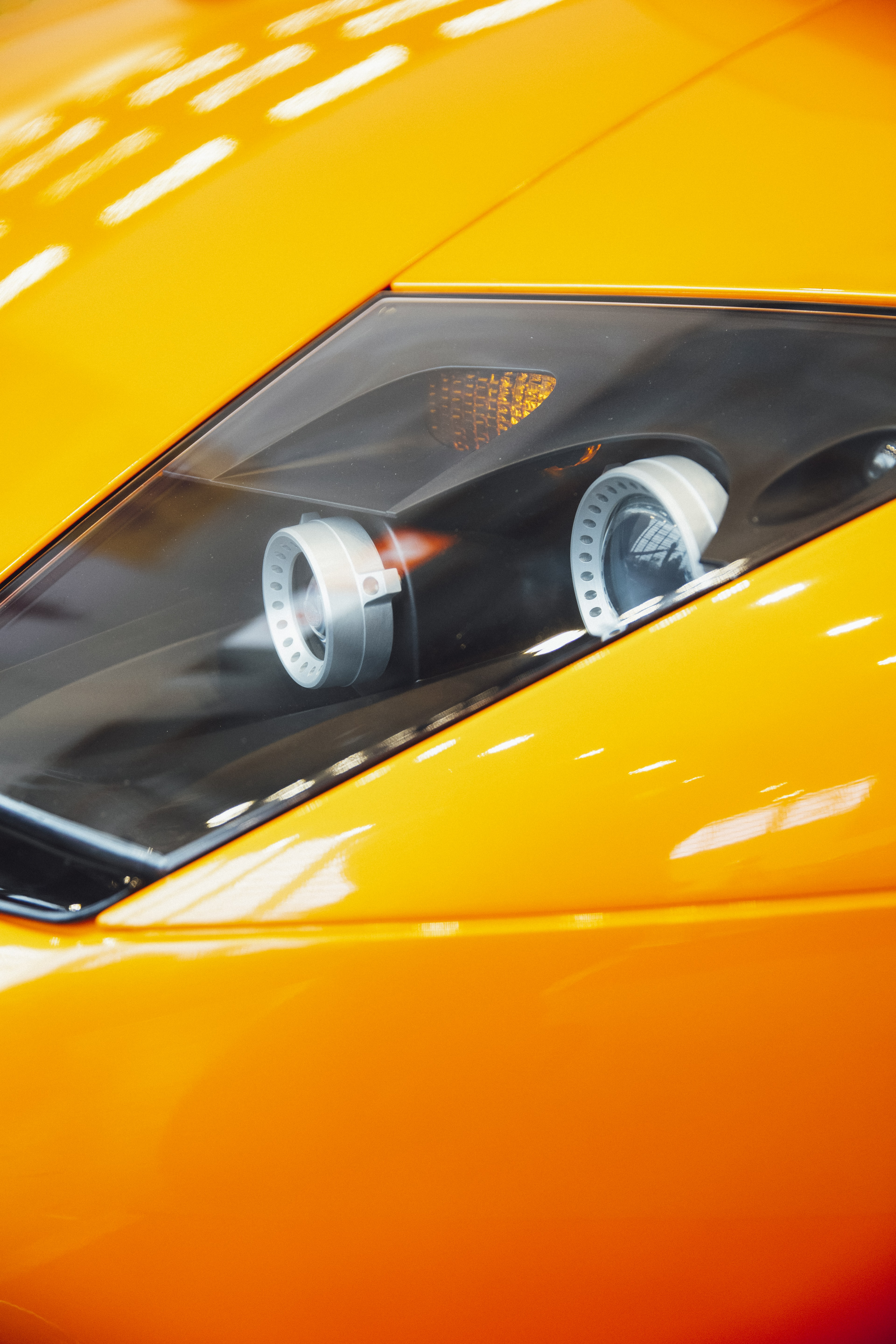 orange sports car with projector headlight