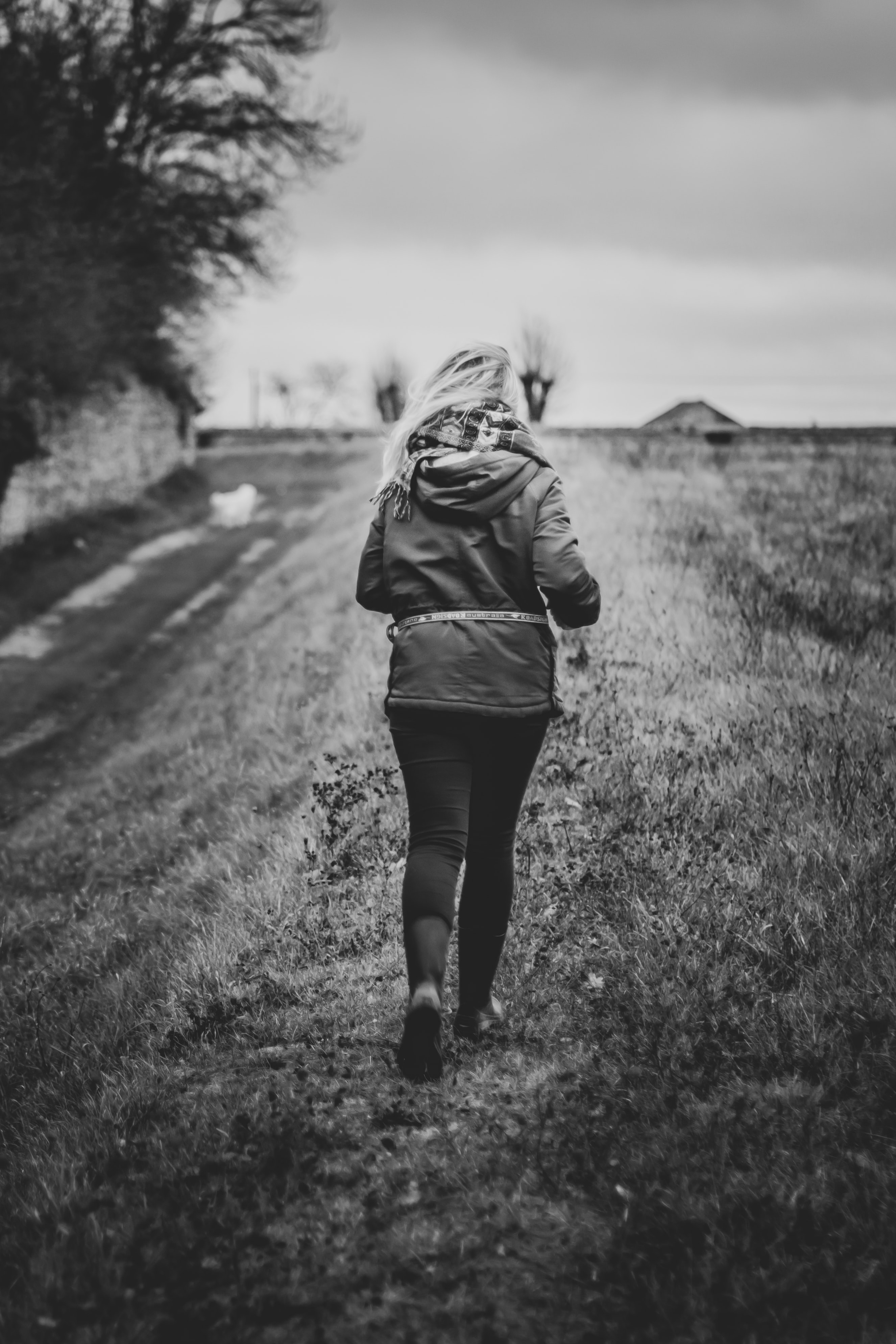 gray scale photography of woman about to run wearing hoodie