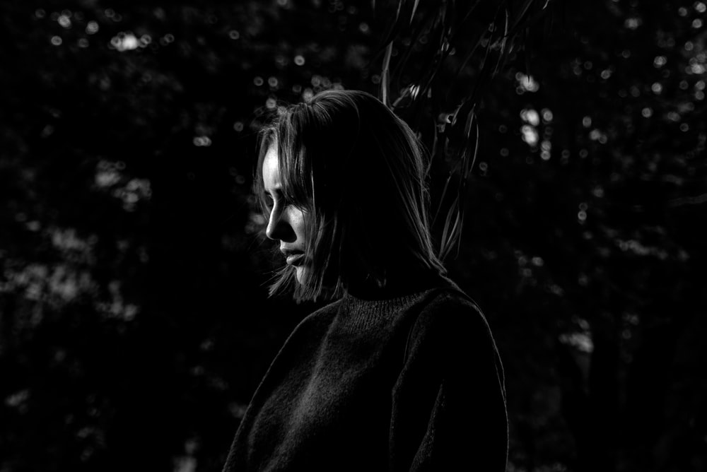 grayscale photo of woman in long-sleeved shirt