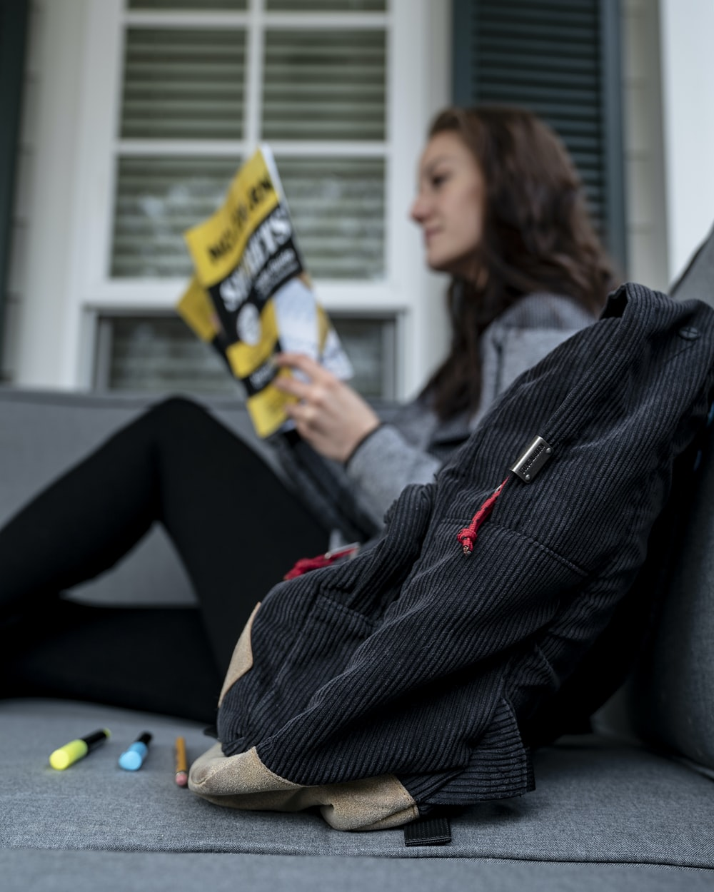 shallow focus photo of black back near woman reading magazine