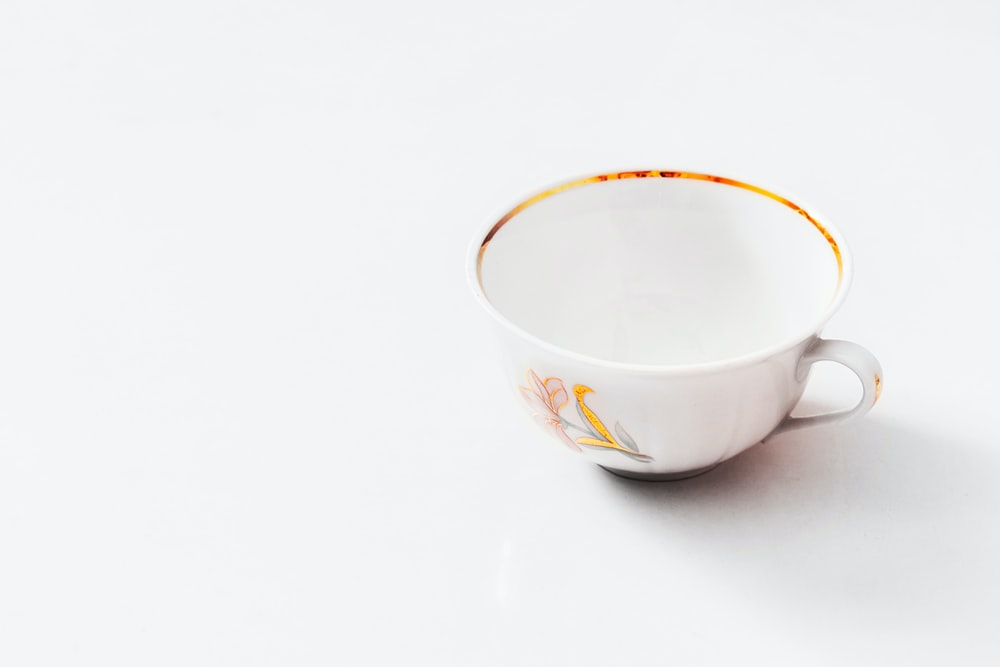 white and yellow ceramic cup