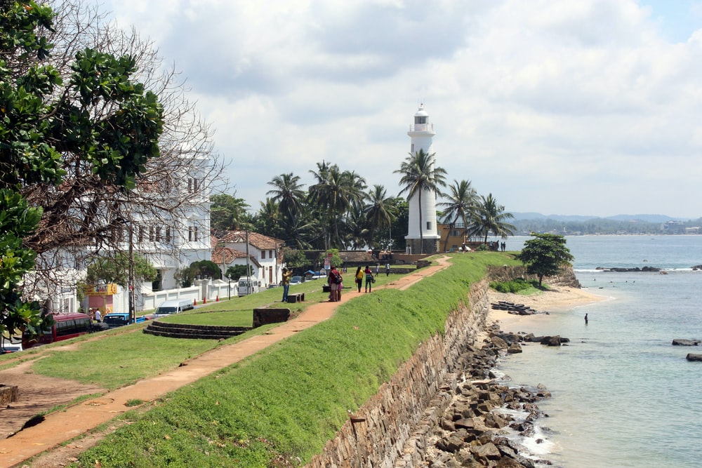white lighthouse near white house