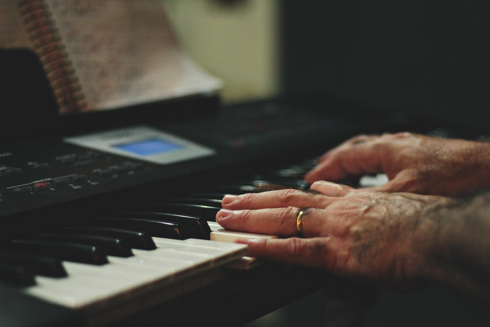 shallow focus photo of person playing piano