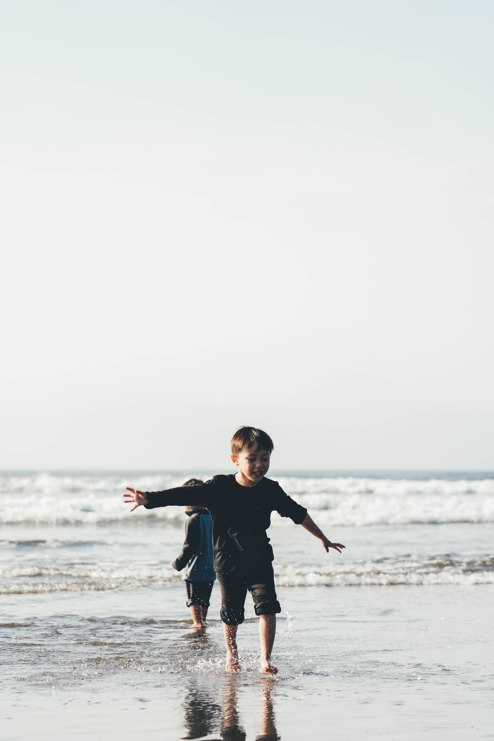 boy wearing long-sleeve top spreading both hands standing on shore