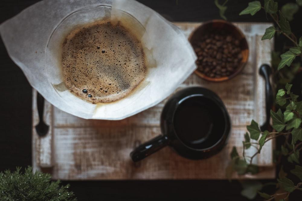black ceramic mug and coffee beans