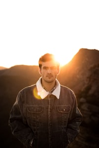 man standing front of mountain during golden hour
