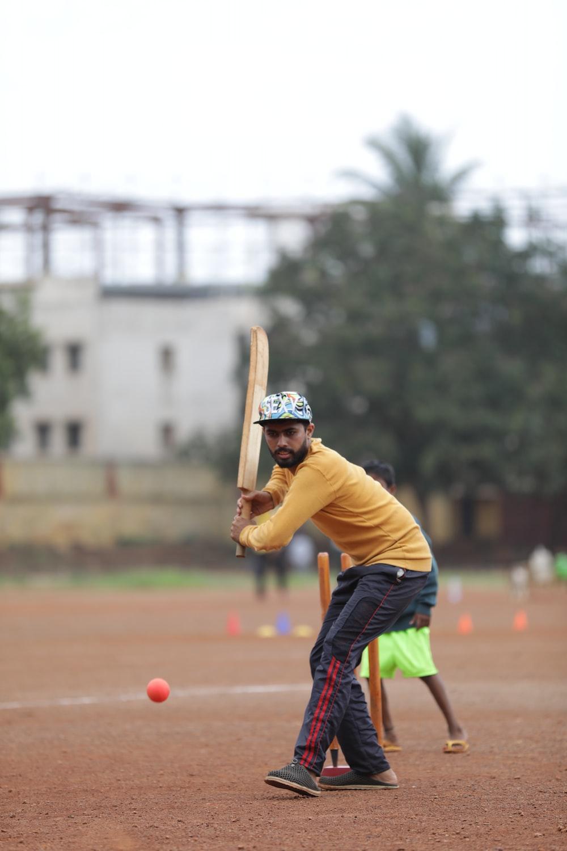 man holding cricket bat on field