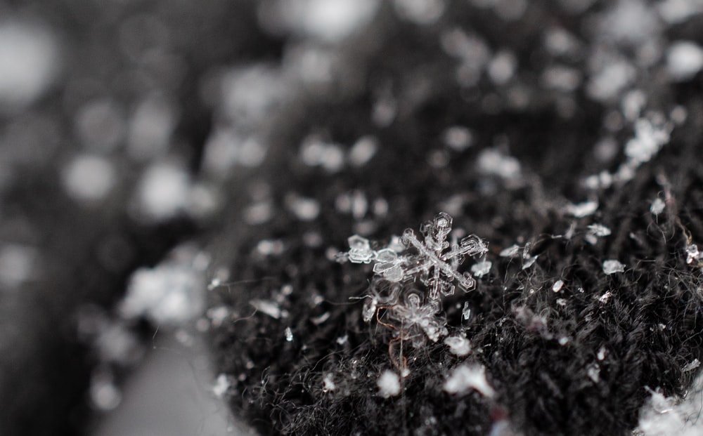 close-up photography of gray textile and snowflakes