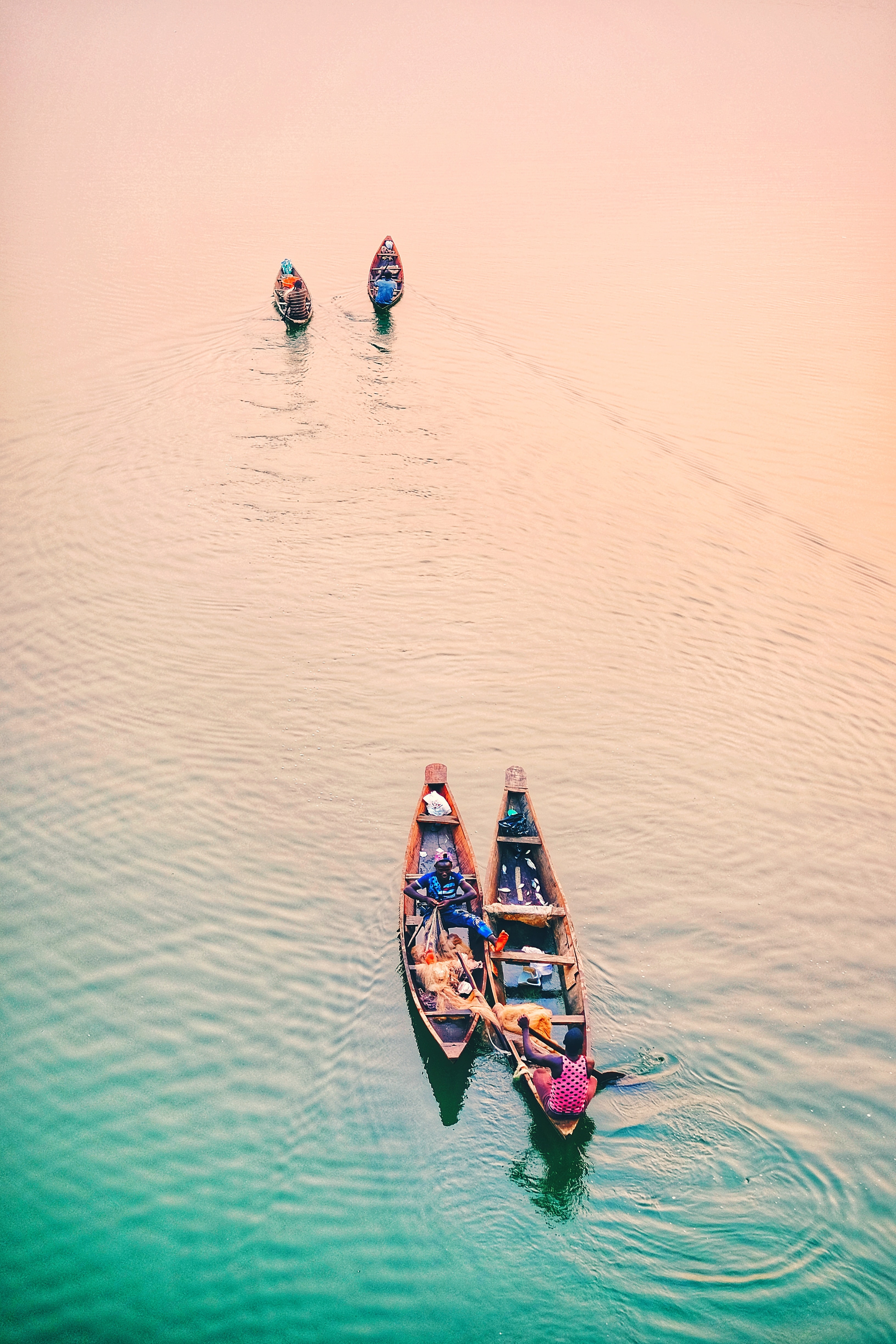 four assorted-color boats on body of water during daytime