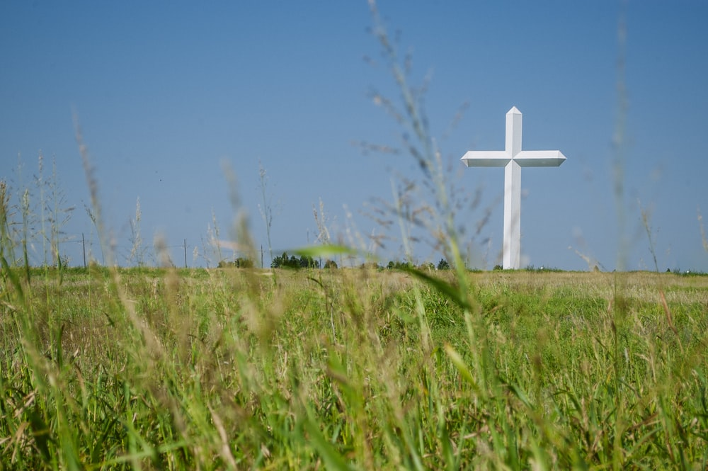 white cross on green field at daytime
