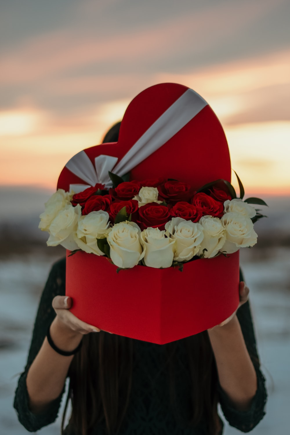 person holding box of roses