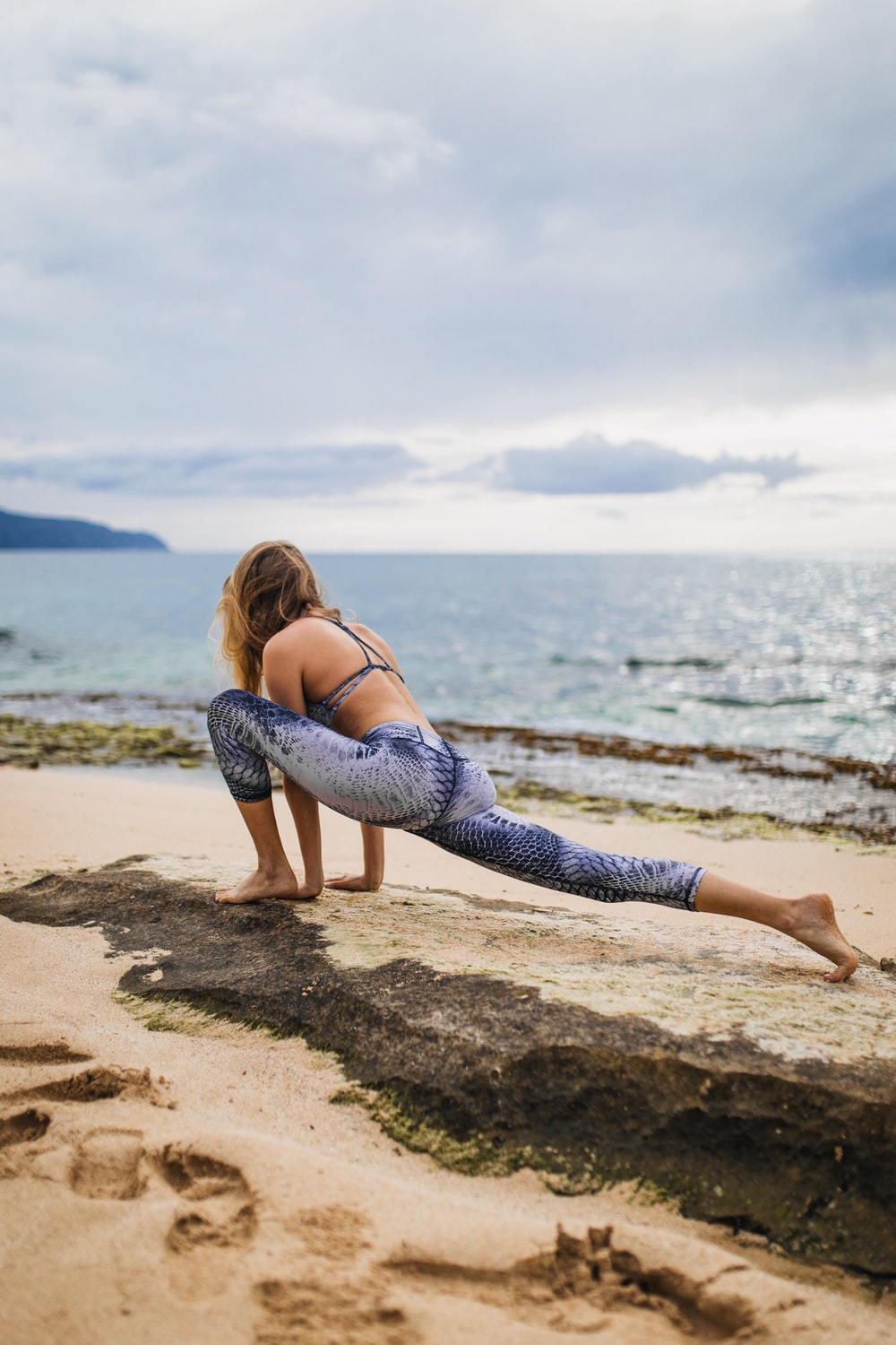 woman stretching beside body of water