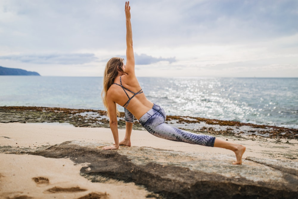 woman stretching front of sea at daytime