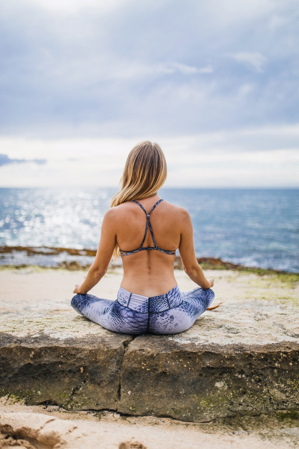 woman meditating front of sea at daytime