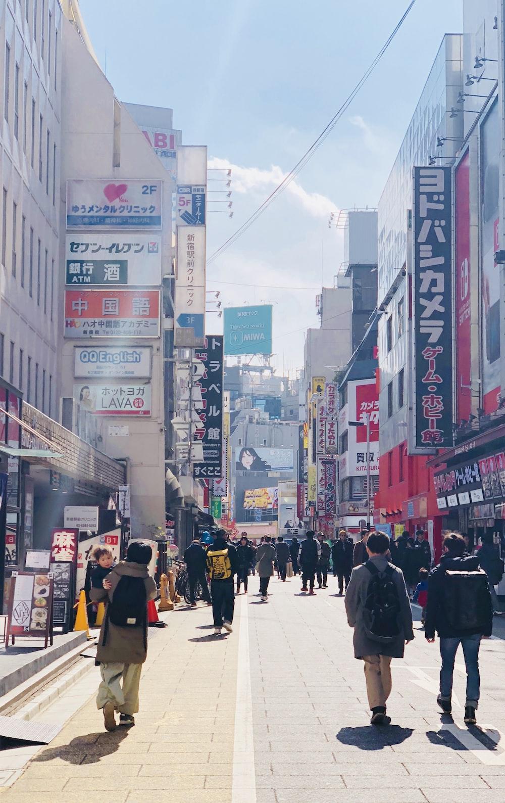 people walking on street in between building during daytime