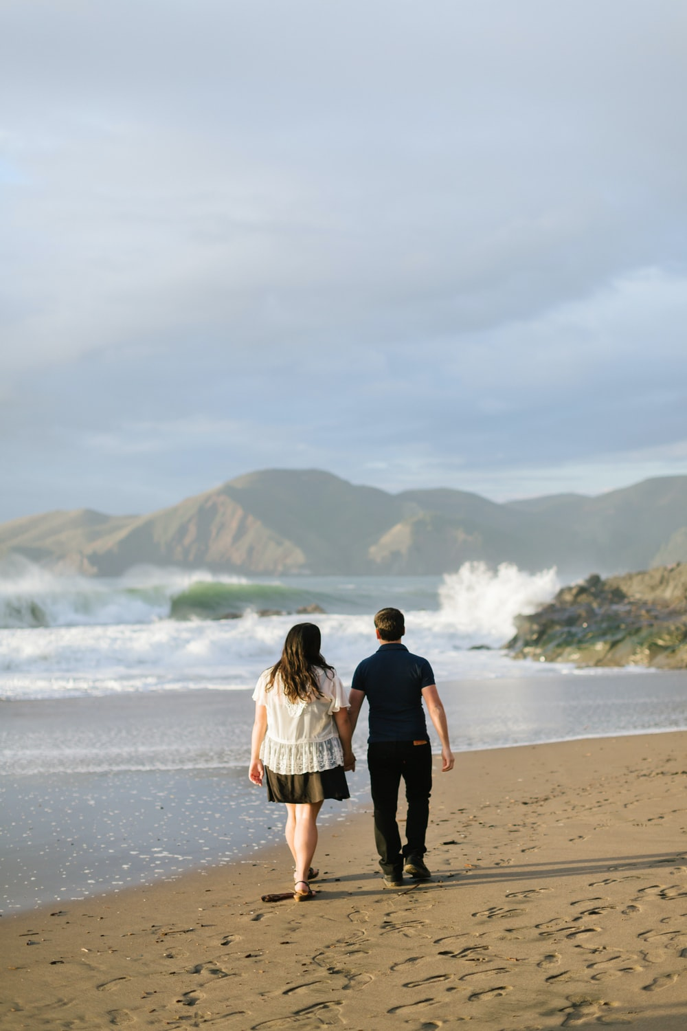 man and woman walking together on seashore
