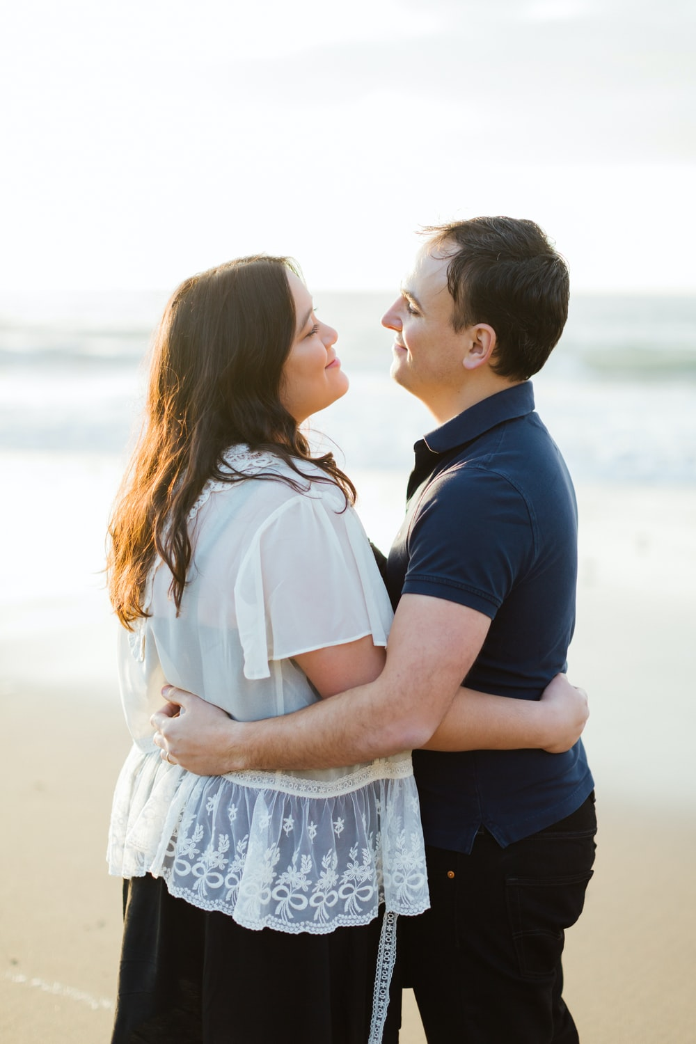 man and woman hugging each other near shoreline during daytime