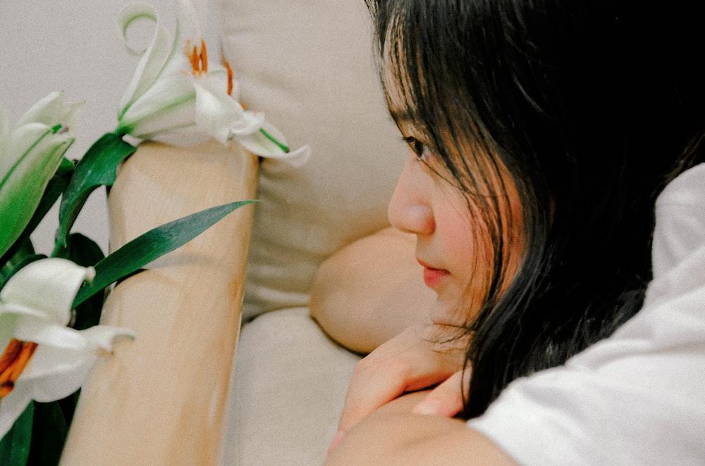 woman lying on white textile near flowers