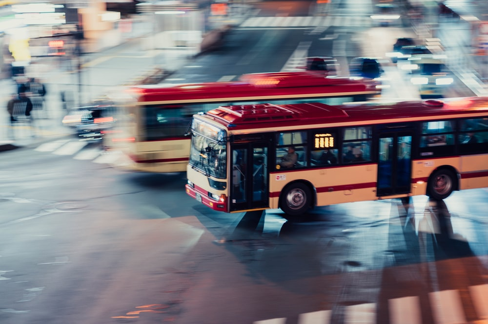 long exposure photography of white and red bus on road