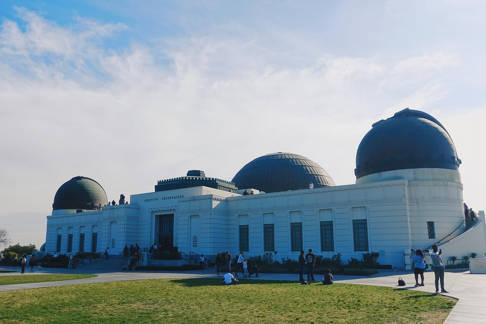 people walking near black and white dome building