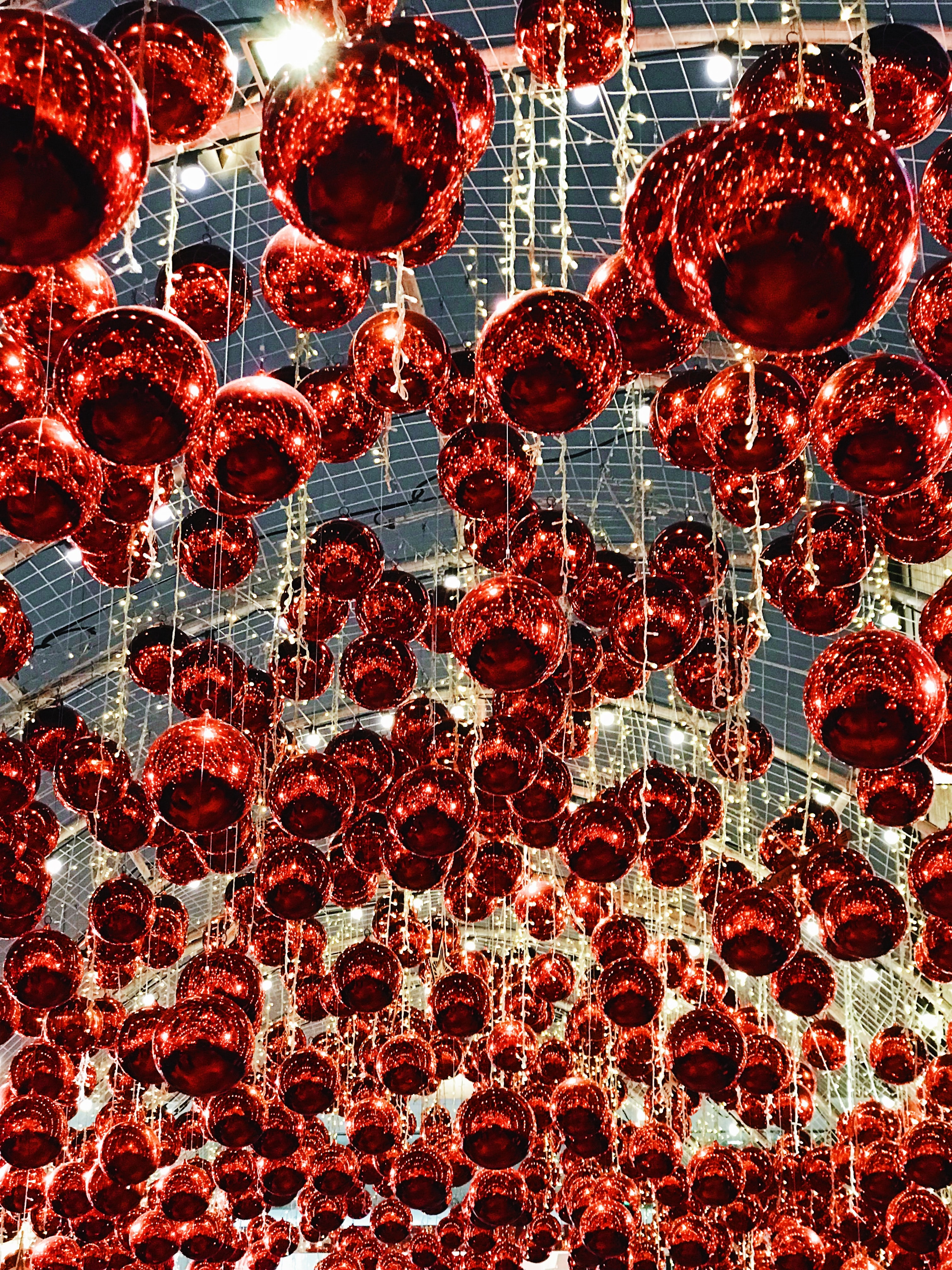 low-angle photography of red lanterns inside gray buildign