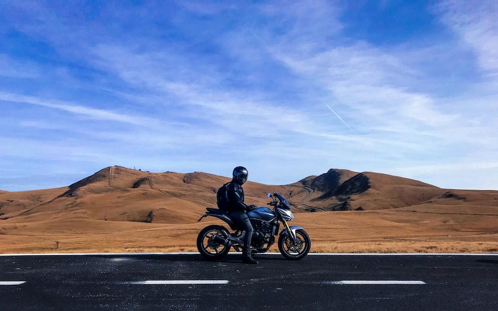 man riding motorcycle at vast land during daytime