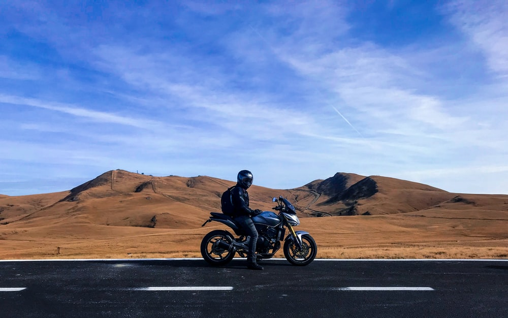 man riding motorcycle at vast land during daytime