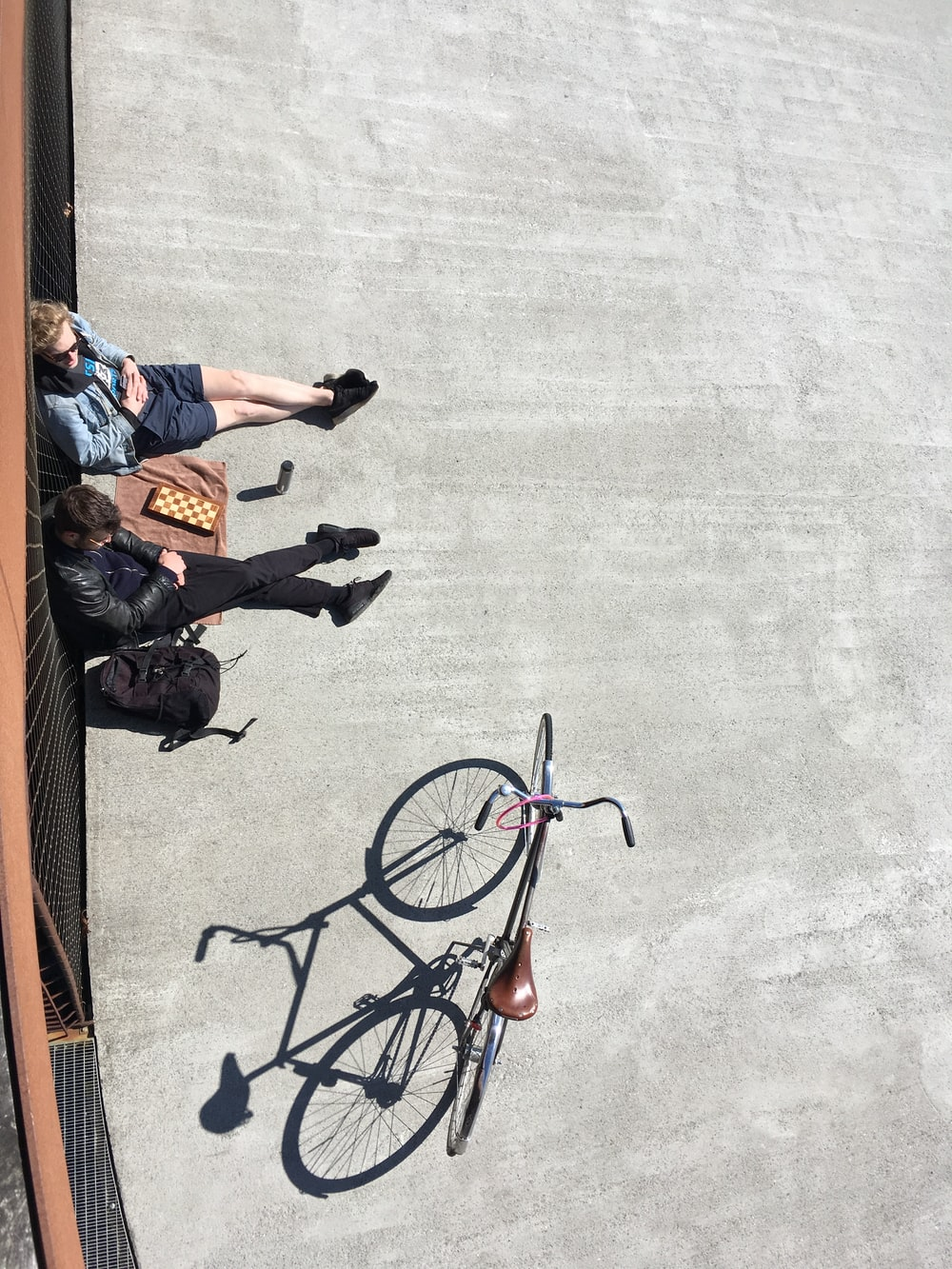 2 person sitting on pavement beside parked bicycle during daytime