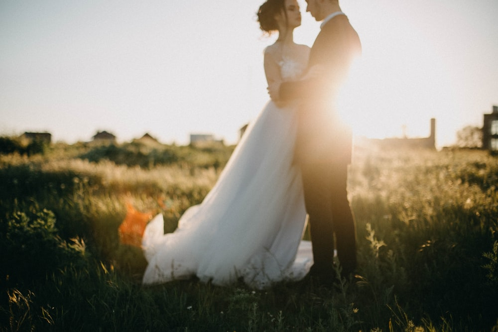 wedded couple face to face with each other on grass field during golden hour