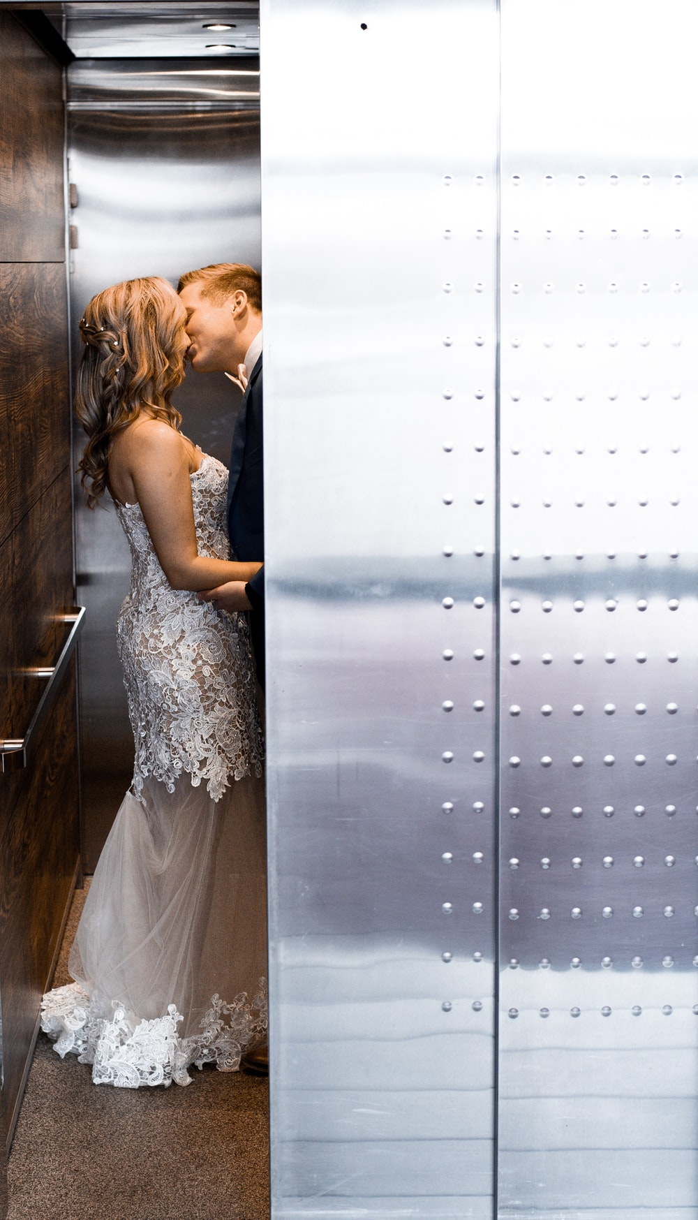 wedding couple kissing behind wall