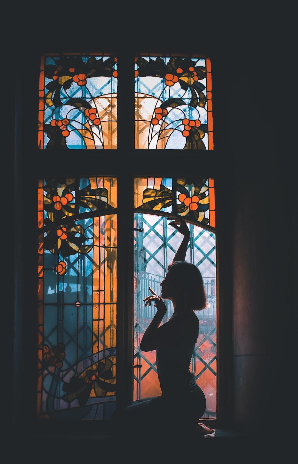 silhouette of woman sitting beside window